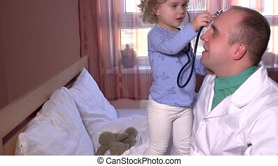 Cute little patient boy playing with his doctor stethoscope in hospital ward bed