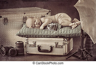 Cute little photographer sleeping on the suitcase