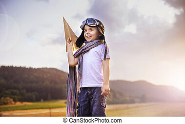 Cute little pilot holding a toy plane