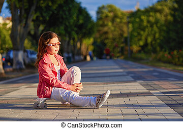 girl wearing helmet sitting on a skateboard in beautiful summer park