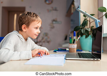 Cute little schoolboy studying at home doing school homework. Distance learning online education