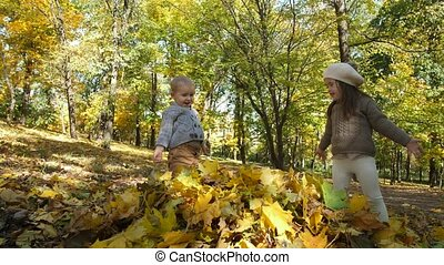 Cute little siblings playing with leaves in park