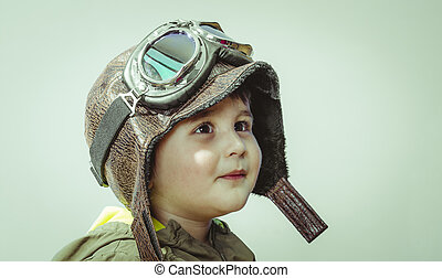Cute little toddler boy, playing at home with playing wars and peace, funny child dressed in militar hat and goggles