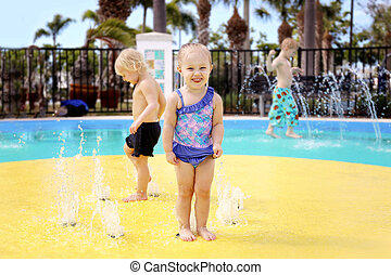 Cute Little Toddler Girl Playing in a Splash Park with Friends Outside on Summer Day