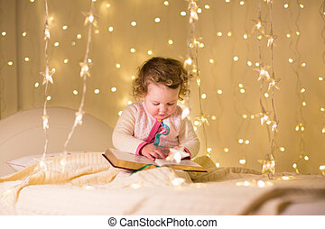 Cute little toddler girl reading a book in a dark room with Chri