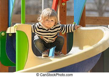 cute little toddler girl sliding down the children's slide