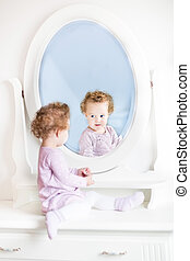 Cute little toddler girl with curly hair looking at her reflecti