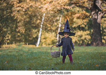 cute little todler giirl witch in hallowem costume in fall ...