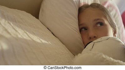 Cute little yawning girl in pajamas lying in a bed under a white blanket on sunny morning
