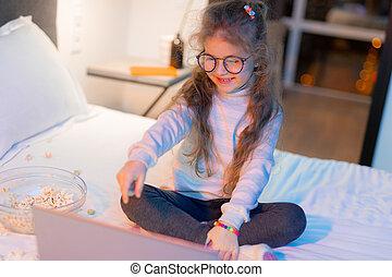 Cute long-haired girl in big eyeglasses watching a movie