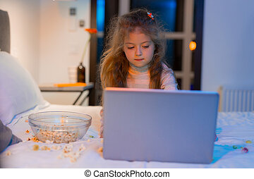 Cute long-haired girl with a bright hairpin playing on a laptop