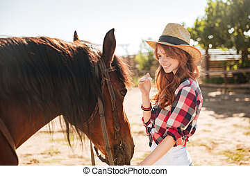Cute lovely cowgirl taking care of her horse on ranch - Cute...