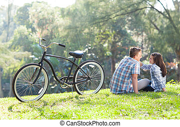 teen couple sitting on the grass