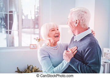 Cute loving couple of pensioners feeling cheerful dancing at home