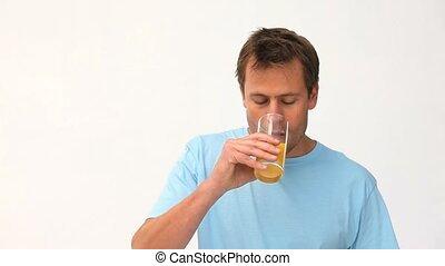 Cute man drinking his glass of orange juice