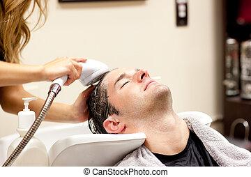 Cute man having a shampoo