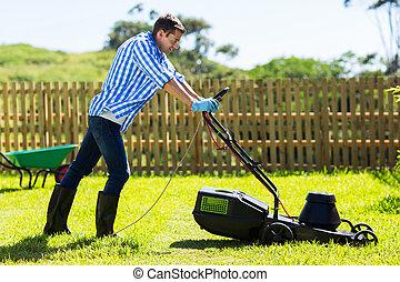 man mowing lawn in the backyard
