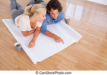 Cute man showing a point on a plan to his fiance