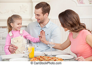 Cute married couple and child have a dinner