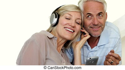 Cute mature couple listening to music