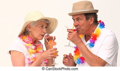 Cute mature couple sipping cocktails