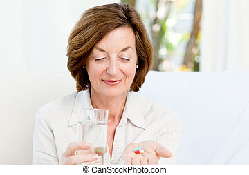 Cute mature woman with pills