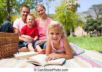 cute, menininha, leitura, mentir grama, enquanto, tendo uma piquenique, com, dela, família, em, um, parque