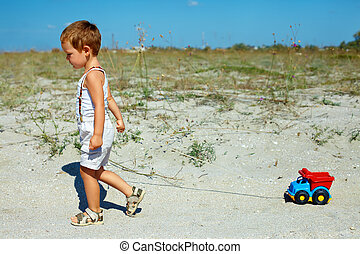 cute, menino bebê, arrastar, carro brinquedo, andar, em, a, campo