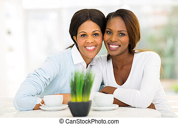 cute mid age african mother and adult daughter having tea at home