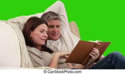 Cute middle-age couple looking at an album