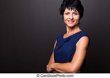 cute middle aged woman portrait on black