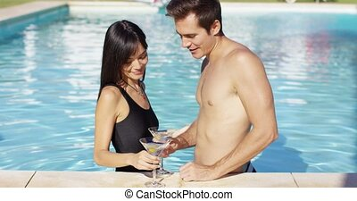 Cute mixed couple holding martini glasses in pool - Cute...