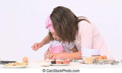 Cute mom baking with her daughter against a white background