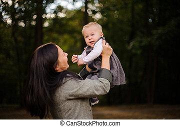cute, morena, filha, mãe, bebê, retrato, tocando, feliz