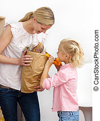 Cute mother and her Little girl unpacking grocery bag in the...