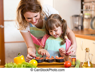 mother with child daughter preparing fish in kitchen