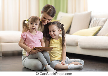 Cute mother with her 2 years old little daughter and 5 years old daughter playing with digital tablet at home