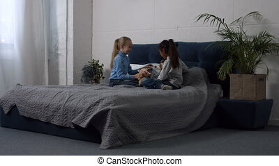 Cute multi ethnic girls playing toys on the bed
