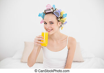 Cute natural brown haired woman in hair curlers drinking orange juice in bright bedroom