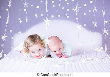 Cute newborn baby and his beautiful toddler sister playing toget