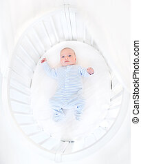 Cute newborn baby boy in a white round crib
