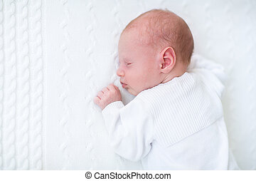 Cute newborn baby boy sleeping on a white knitted blanket
