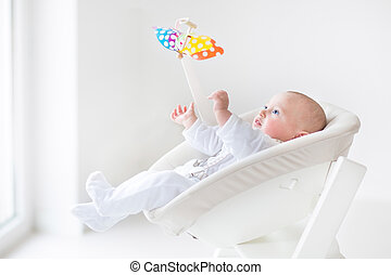 Cute newborn baby boy watching a colorful mobile toy sitting in