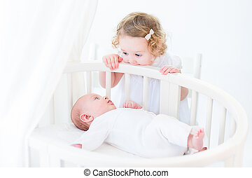 Cute newborn baby boy watching his toddler sister standing at hi