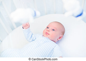 Cute newborn baby boy watching toys in a white round crib