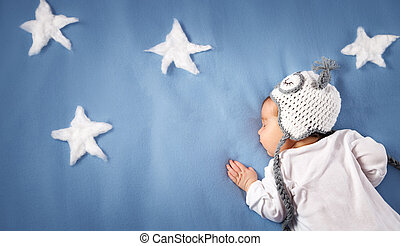 Cute newborn baby girl lying in the bed. 2 month old child in owl hat sleeping on blue blanket