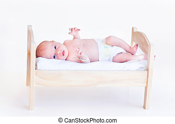 Cute newborn baby in a diaper laying in a toy bed