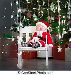 Cute newborn baby in a santa costume and hat sitting in a white