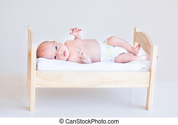 Cute newborn baby in a toy bed