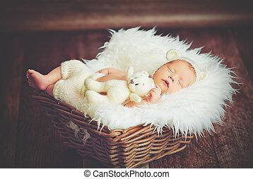 Cute newborn baby in bear hat sleeps in basket with toy teddy bear